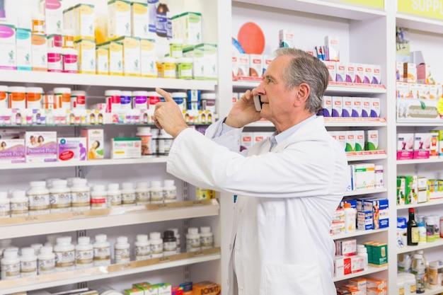 Farmacêutico focado no telefone apontando remédio