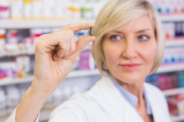Farmacêutico loiro em blusões de laboratório que mostra uma pílula