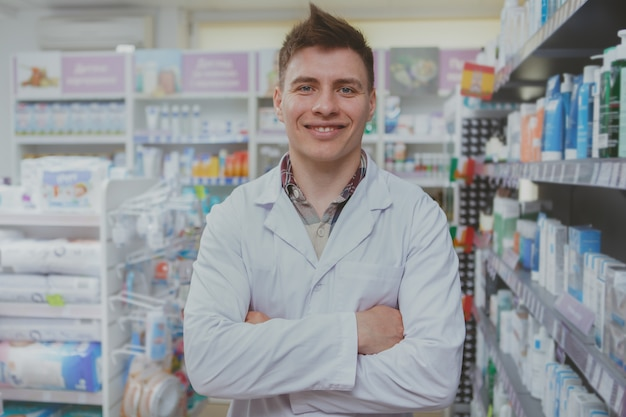Farmacêutico masculino bonito, trabalhando em sua farmácia