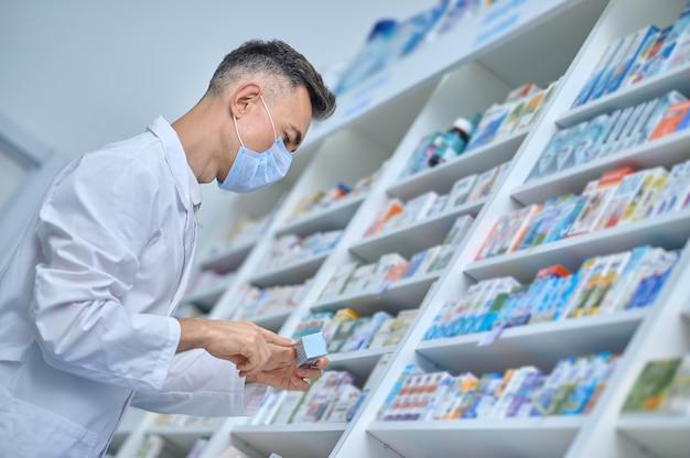 Farmacêutico masculino com máscara protetora focado na leitura do rótulo da caixa de papelão com medicamento