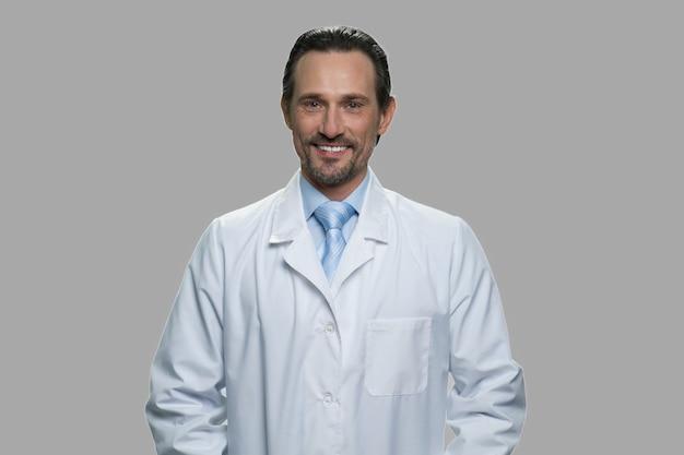 Farmacêutico masculino feliz olhando para a câmera em fundo cinza. retrato do engenheiro sorridente no jaleco.