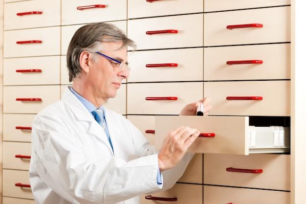 Farmacêutico na frente do armário de remédios