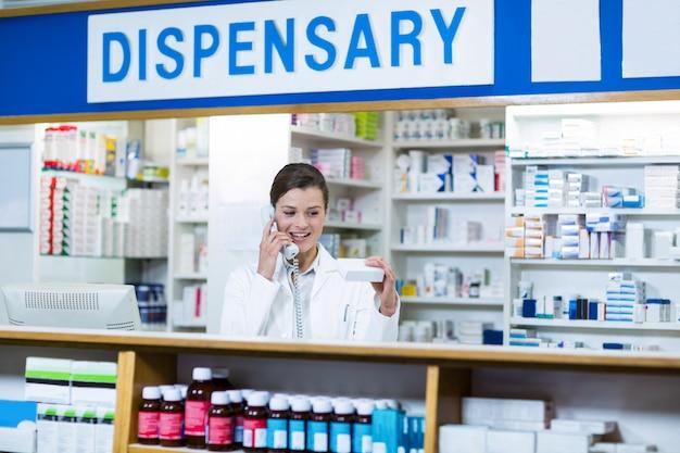 Farmacêutico, olhando para a caixa de medicamento enquanto fala no telefone