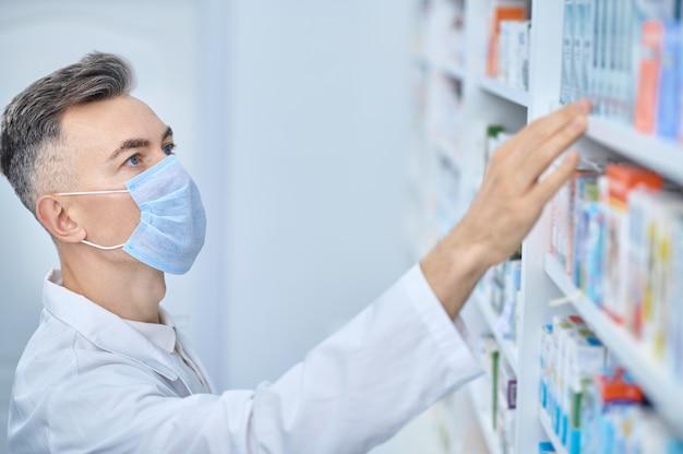 Farmacêutico procurando remédio na prateleira