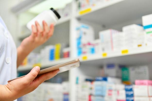 Farmacêutico que guarda a garrafa da medicina e a tabuleta do computador para a prescrição de enchimento na drograria da farmácia.