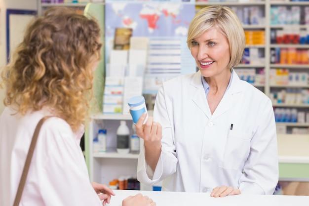 Farmacêutico que mostra o frasco de medicamentos ao figurinista