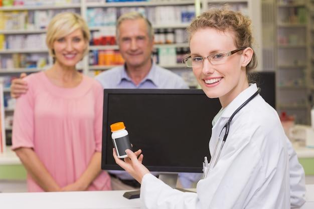 Farmacêutico que mostra o frasco de medicamentos para um cliente