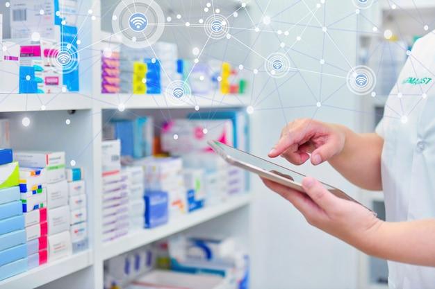 Farmacêutico que segura o tablet do computador e usa para preencher uma receita em uma drogaria de farmácia