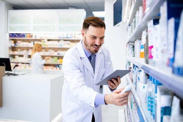 Farmacêutico que trabalha em uma drogaria e segurando medicamentos.