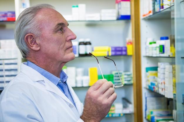 Farmacêutico que verifica medicamentos na farmácia