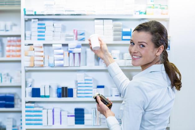 Farmacêutico que verifica o medicamento na prateleira na farmácia