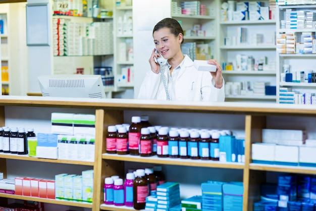 Farmacêutico segurando a caixa do medicamento enquanto fala no telefone