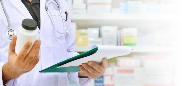 Farmacêutico, segurando o frasco de medicamento e tablet computador para preenchimento de prescrição em farmácia farmácia