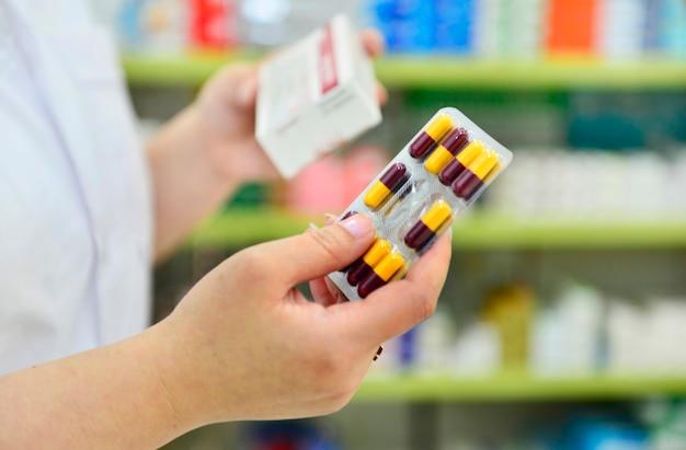 Farmacêutico segurando o pacote de cápsulas e a caixa de remédios na drogaria da farmácia.