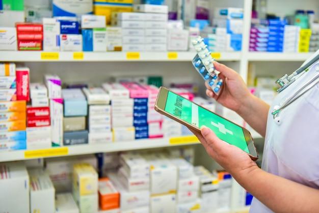 Farmacêutico segurando o tablet computador usando para preencher a prescrição em farmácia farmácia