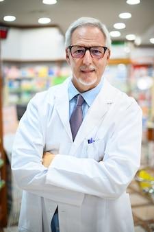 Farmacêutico sênior sorrindo e cruzando os braços em sua loja