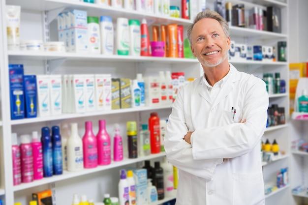 Farmacêutico sênior, sorrindo e olhando para cima na farmácia