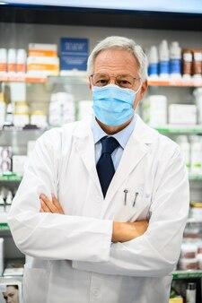 Farmacêutico sênior usando máscara devido à pandemia de coronavírus em sua loja