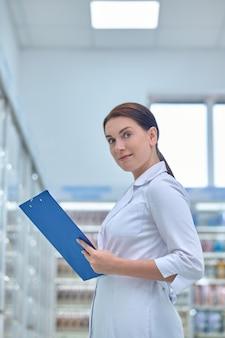 Farmacêutico sereno e bonito vestido com um robe branco limpo parado entre as vitrines da farmácia