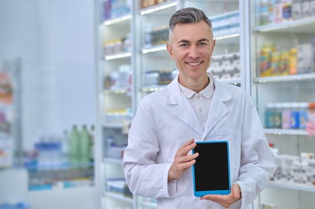 Farmacêutico sorridente ao lado da vitrine da drogaria