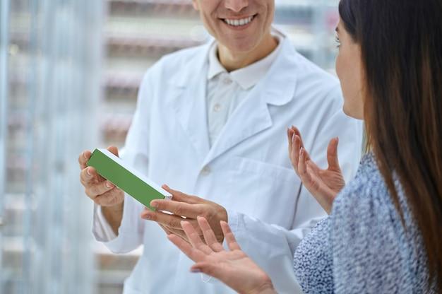 Farmacêutico sorridente com produto médico e mulher gesticulando