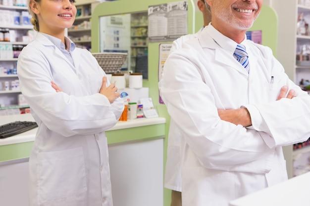 Farmacêutico sorridente e seu estagiário com os braços cruzados
