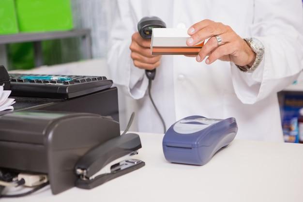 Farmacêutico usando máquina e segurando medicamento