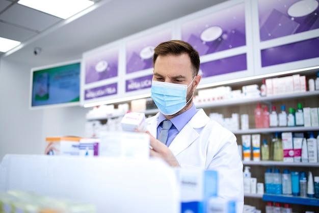 Farmacêutico usando máscara facial e jaleco branco, trabalhando em loja de farmácia durante a pandemia do vírus corona, organizando medicamentos na prateleira