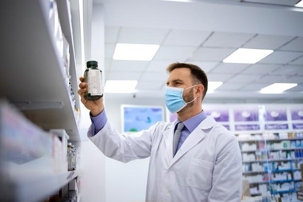 Farmacêutico usando máscara facial e tomando vitaminas da prateleira da farmácia durante a pandemia covid19
