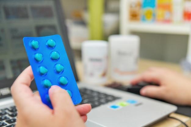 Farmacêutico usando o laptop do computador na farmácia ou farmácia. mão segurando o pacote de remédios e chave a ordem de prescrição.