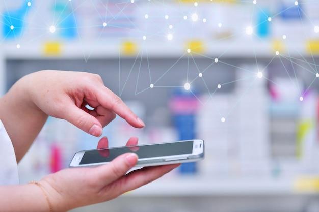 Farmacêutico usando smartphone móvel para barra de pesquisa em exibição nas prateleiras das drogarias de farmácias