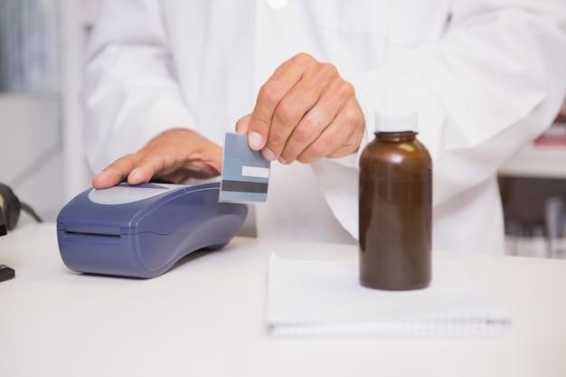 Farmacêutico usando teclado com cartão de crédito