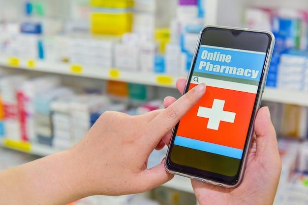 Farmacêutico usando telefone móvel inteligente para barra de pesquisa em exposição no fundo de prateleiras de farmácia de farmácia. conceito médico online.