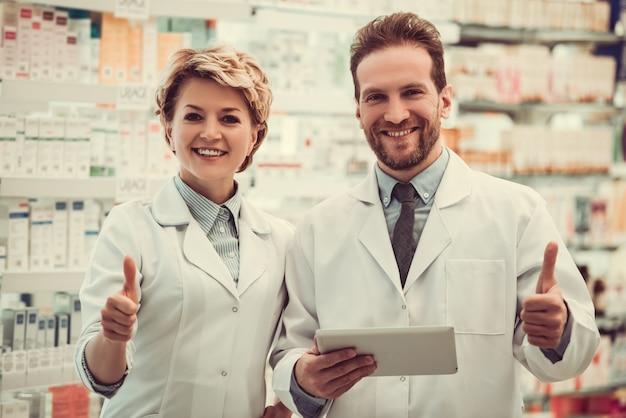 Farmacêuticos bonitos estão mostrando os polegares.