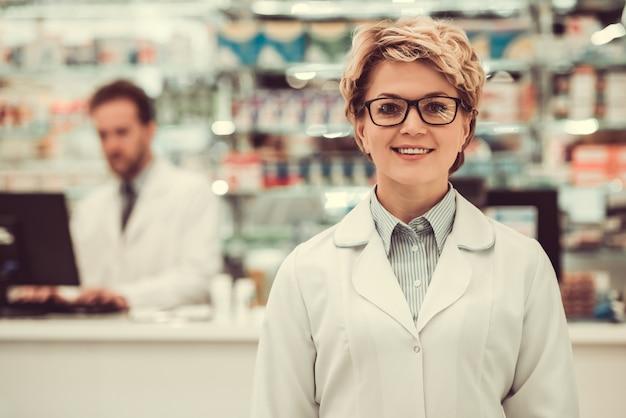 Farmacêuticos bonitos que trabalham na farmácia.