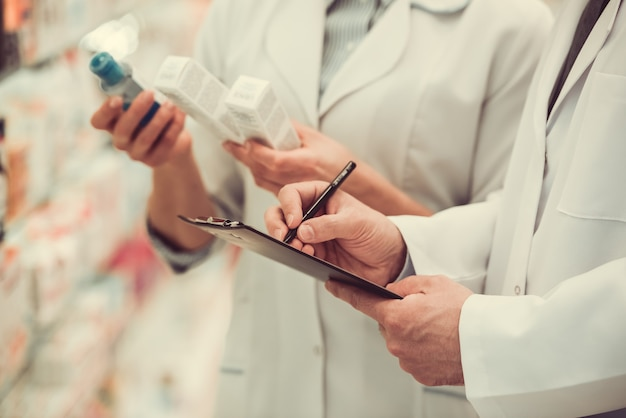 Farmacêuticos bonitos que verificam a medicina e que tomam notas.