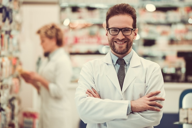 Farmacêuticos consideráveis que trabalham na farmácia.
