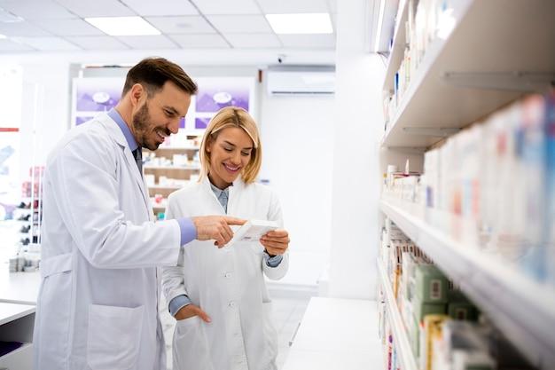 Farmacêuticos que se consultam sobre medicamentos em farmácias.