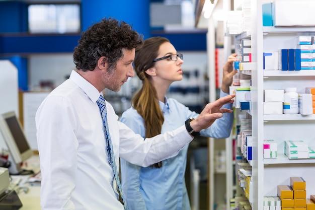 Farmacêuticos que verificam medicamentos na prateleira na farmácia