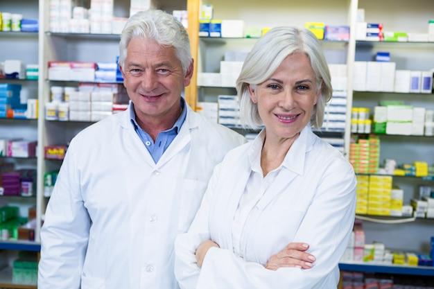 Farmacêuticos sorridentes em pé na farmácia