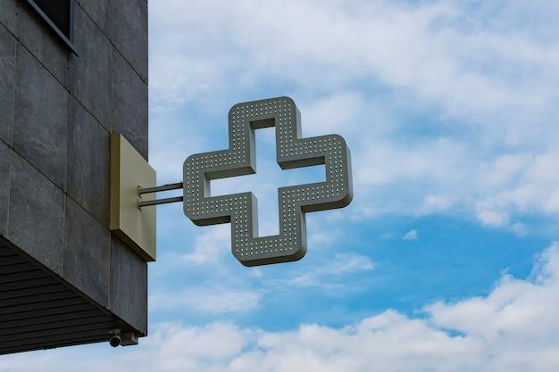 Farmácia cruzar em segundo plano contra o céu com nuvens.