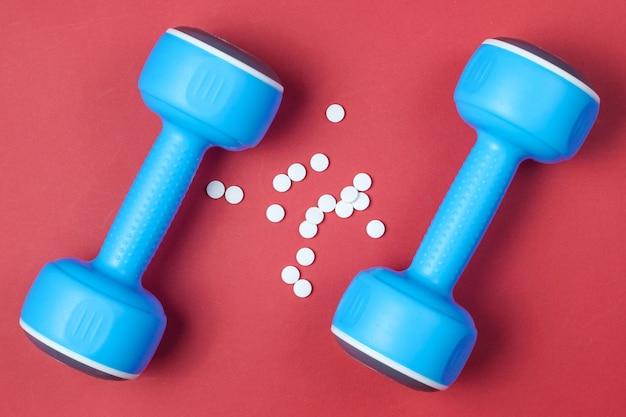 Farmácia esportiva. halteres de plástico, comprimidos em fundo vermelho. vista do topo.