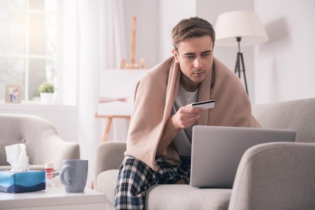 Farmácia na internet. homem doente e desanimado segurando seu cartão de crédito enquanto compra remédios online