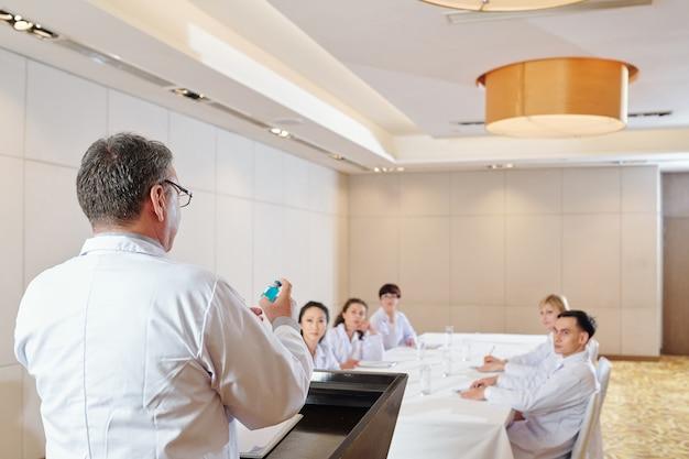 Farmacologista falando sobre a nova vacina covid-19 em conferência com jovens especialistas