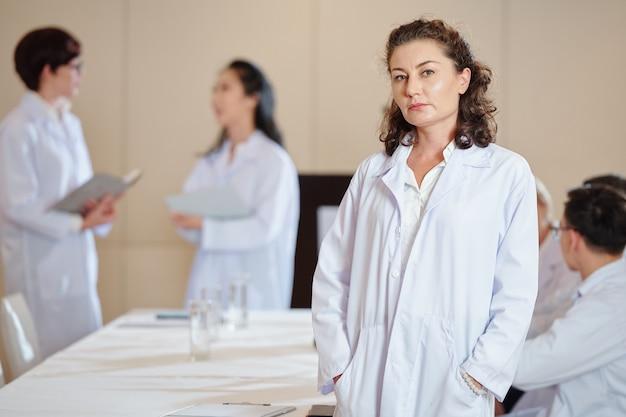Farmacologista feminina madura séria em jaleco, em pé à mesa na sala de reuniões e olhando para a câmera