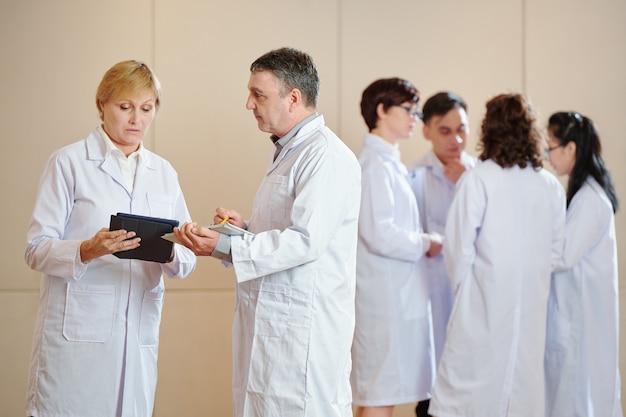 Farmacologistas sérios e experientes discutem os resultados da pesquisa em um tablet, seus jovens colegas conversando em segundo plano