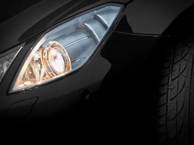 Faróis de um carro preto. fragmento