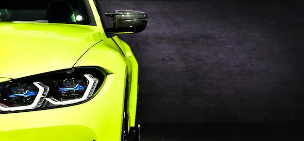 Faróis dianteiros de um carro esporte moderno verde em fundo preto