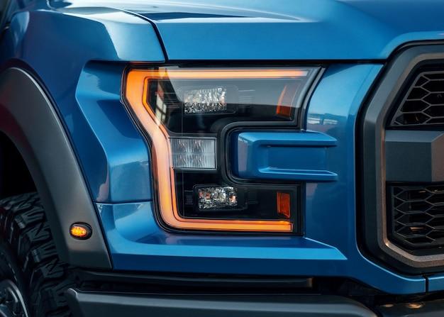 Faróis dianteiros iluminados de um suv moderno azul