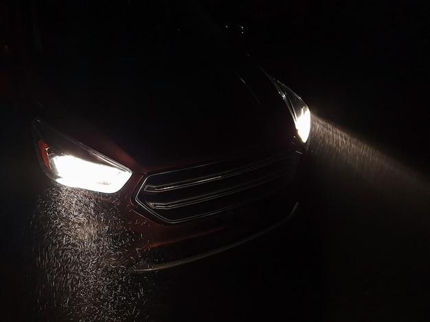 Faróis do carro brilham em uma forte nevasca